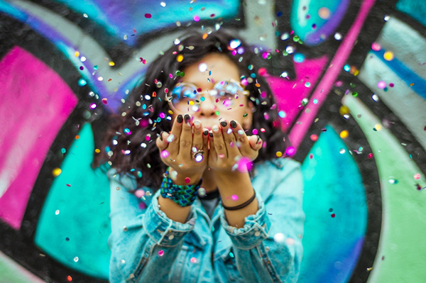 Een meisje dat confetti naar de kijker blaast tegen een achtergrond van vrolijke graffiti.