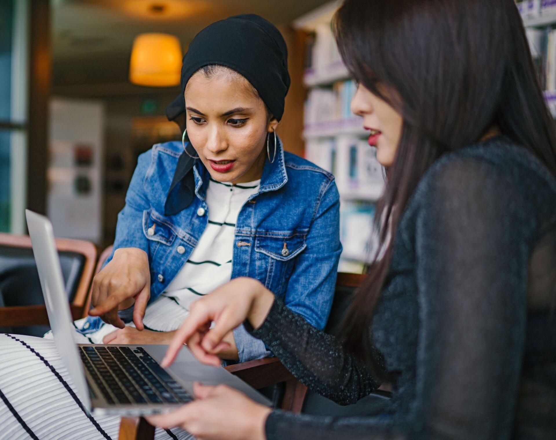 2 vrouwen kijken naar een laptop