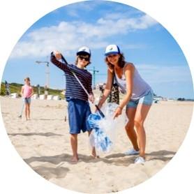 jongen en vrouw met petjes op het strand, met een vuilniszak vol afval