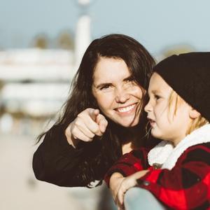 Vrouw samen met haar kind, vrouw lacht en wijst richting de camera